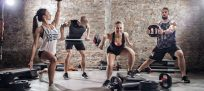 Group of fit and muscular people practicing with barbell on urban place