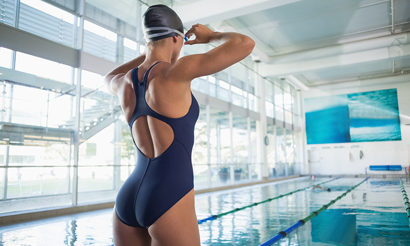 Rear view of a fit swimmer by pool