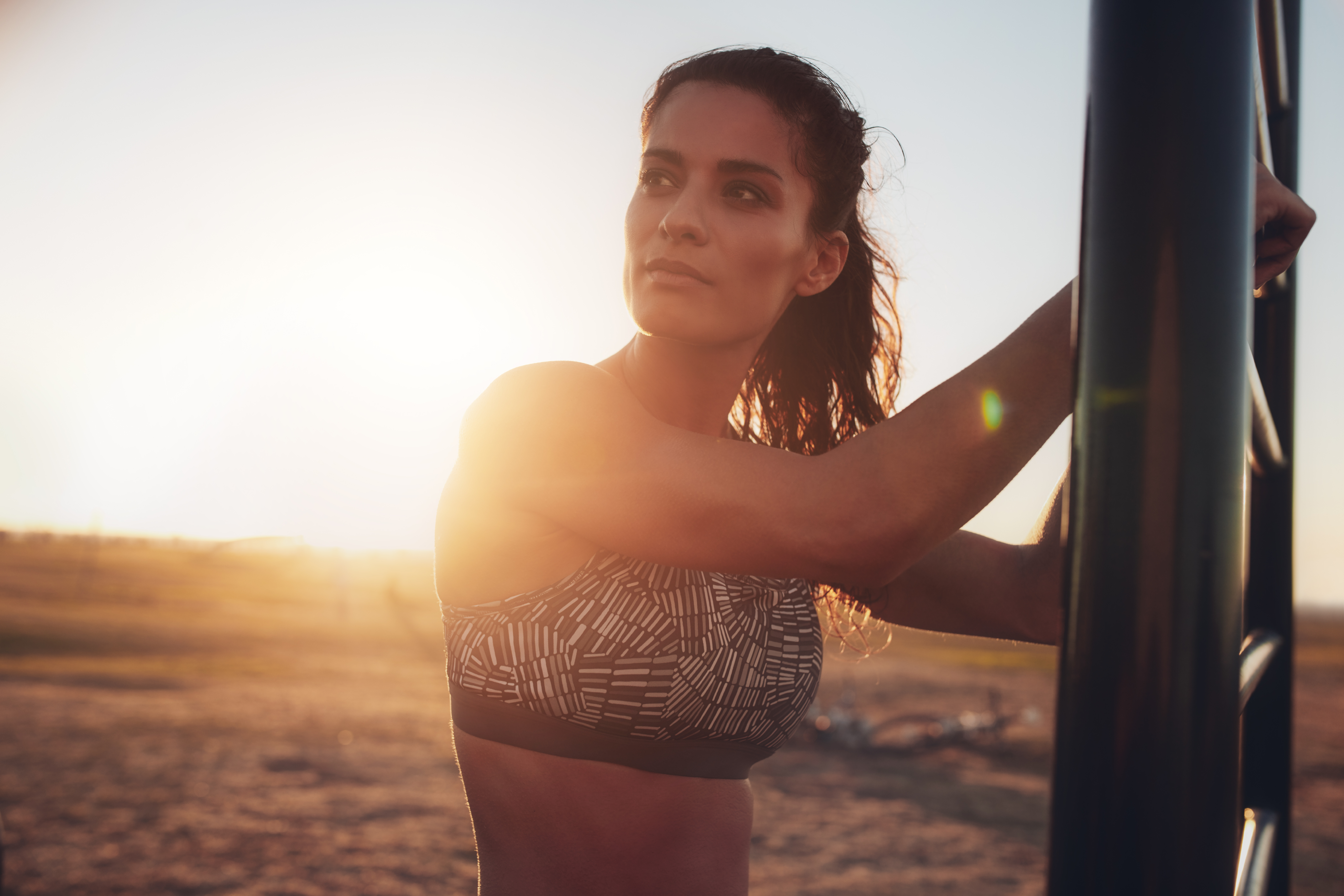 Fitness woman standing outdoors and looking away
